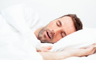 Man snoring while sleeping in bed