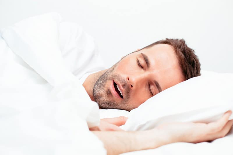 Man laying on his side, snoring. His sleep apnea could be related to a number of health issues including acid reflux or diabetes.