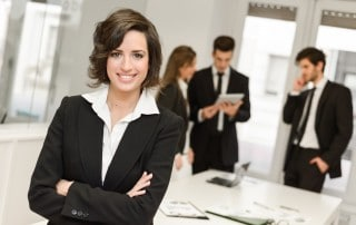 Business woman in a suit smiling with her arms crossed while three coworkers speak with each other in the background