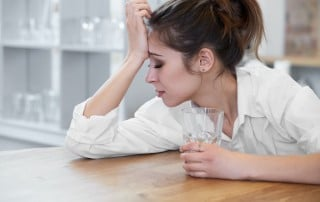 Young woman with a pony tail holding a glass of water and holding her head in pain while leaning on a table