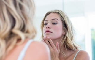 Woman looking at self in mirror and touching her chin