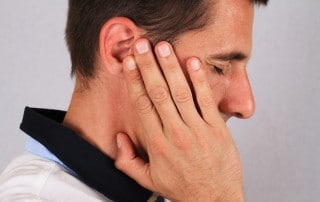 Sideview of man holding his jaw in pain