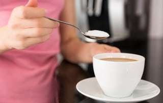 Close up of woman putting a spoonful of sugar into coffee