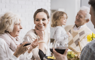 A family laughing and drinking wine