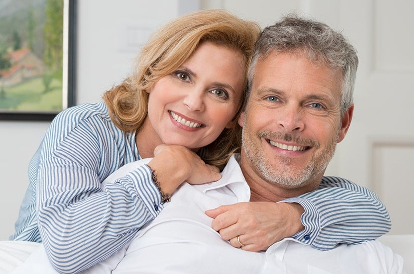 mature woman hugging her husband around the neck as he sits on the couch