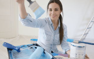 A female making home improvements by painting a room.