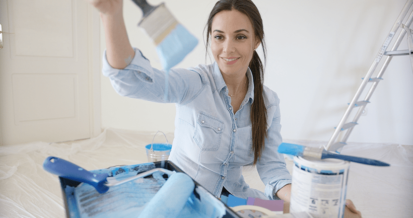 A female making home improvements by painting a room. She has also recently improved her smile at the Rochester, MI dental office of Dr. Kurt Doolin
