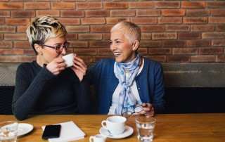 Senior mother sitting in cafe bar or restauant with her middle age daughter and enjoying in conversation - something she can only do because of a new dental implant procedure.