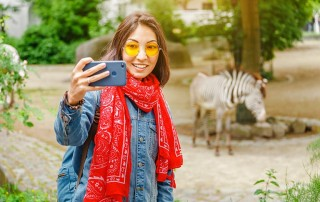 Young woman safely taking a selfie with zebra in the background