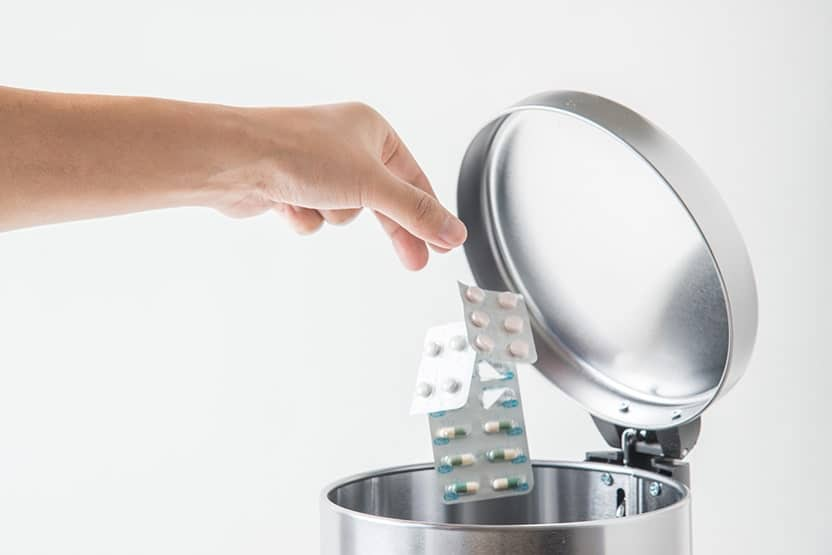 A hand throwing away a few pack of pills into a steel trashcan. If you're looking into dental implants you may not need to stop your bisphosphonates.