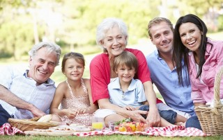 A multi-generational family enjoying a fun time outside at a picnic. It's being said that genetic variations can affect your teeth and oral health.