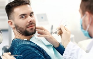 A young man sitting in a dental chair, scared about seeing his dentist for a cleaning. If you have anxiety over seeing a cosmetic dentist concern sedation dentistry with Dr. Haddad and Dr. Doolin of Rochester Advanced Dentistry.