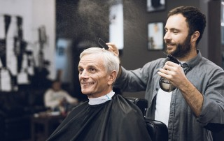 a barber sprays water into an older male's hair as he gets a haircut