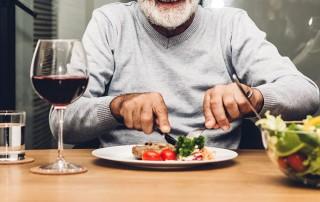 Senior man cutting up his steak in a restaurant