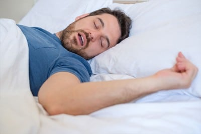 man snoring loudly while sleep in bed