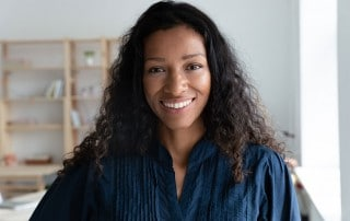 woman with a wide smile and curly black hair