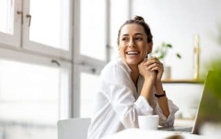 young woman sitting at her computer, drinking coffee during the day