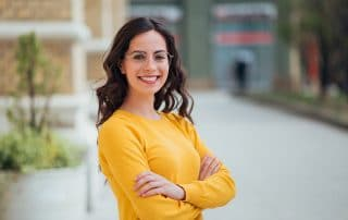 confident young woman in yellow shirt shows off her amazing smile